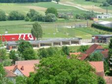 Blick zum Schulgebäude mit den beschatteten Freiflächen vor jeder Klasse, die einem ungestörten Freiluft-Unterricht dienen. Foto: Gemeinde Bad Blumau (Stand Ende Mai 2010).